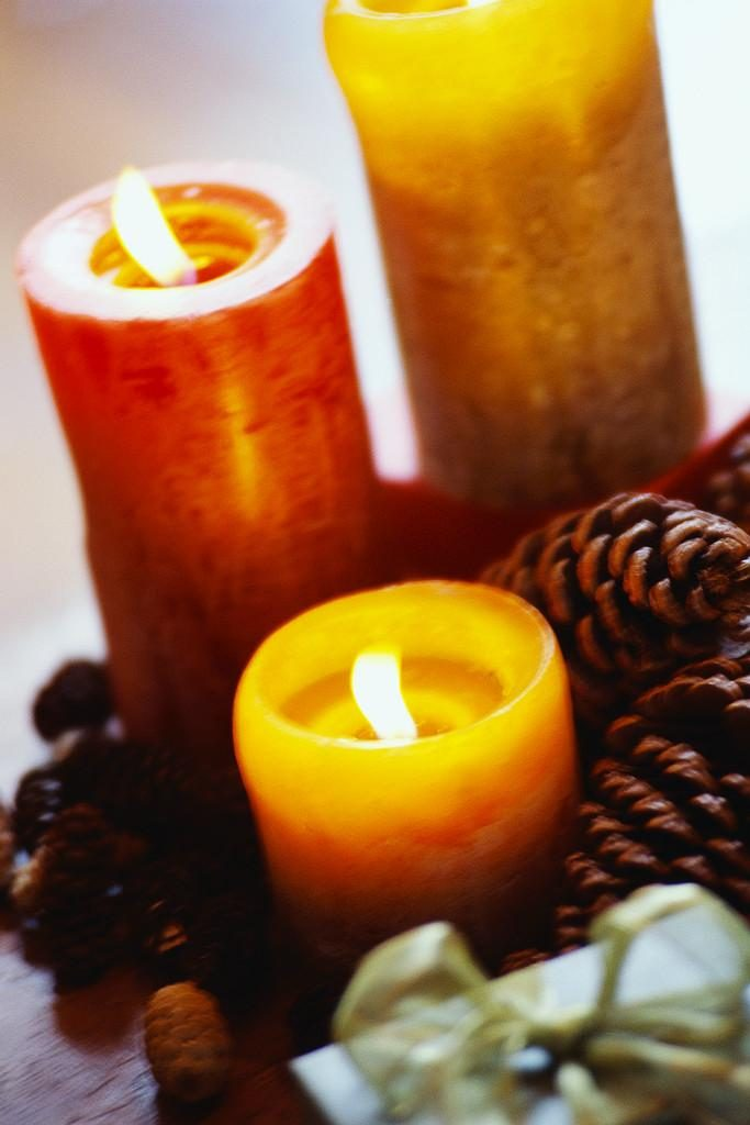 three lit candles with pine cones
