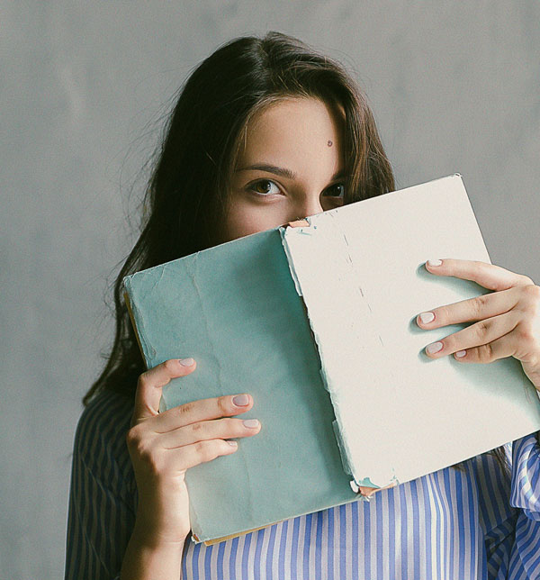 young woman holding a book in front of her face